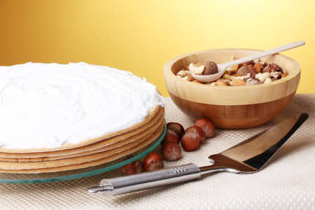 cake on glass stand and nuts on table on yellow background photo