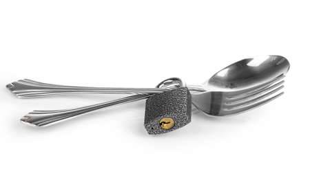 Fork and spoon with padlock isolated on white photo
