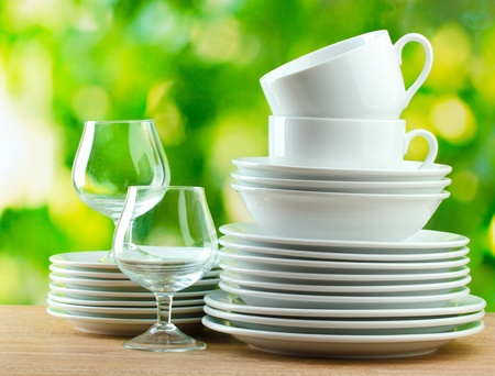 Clean dishes on wooden table on green background Stock Photo - 12664876