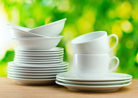 Clean dishes on wooden table on green background Stock Photo - 12664903