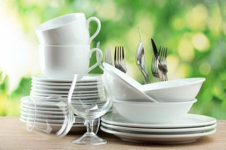 Czyste naczynia na drewnianym stole na zielonym tle