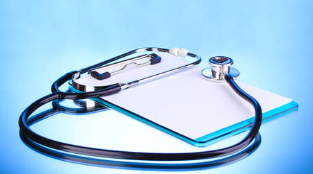 Medical stethoscope and clipboard on blue background photo