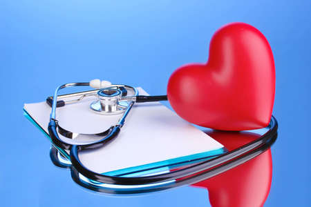 Medical stethoscope with clipboard and heart on blue background Stock Photo - 12664905