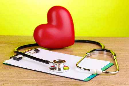 Medical stethoscope with clipboard and heart on wooden table on green background photo