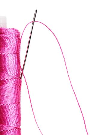 pink bobbin thread with needle isolated on white  photo