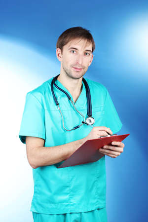 young doctor man with stethoscope and folder on blue backgrounds  Stock Photo - 12664879