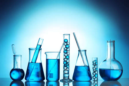 Test-tubes with blue liquid on blue background Stock Photo - 12664698