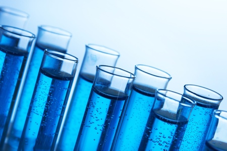 Test-tubes with blue liquid on blue background photo