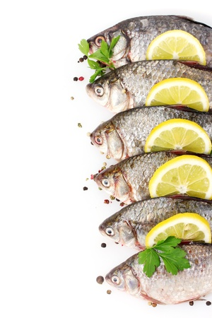Fresh fishes with lemon, parsley and spice isolated on white Stock Photo - 12664915