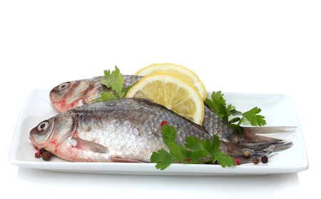 Fresh fishes with lemon and parsley on plate isolated on white Stock Photo - 12664373