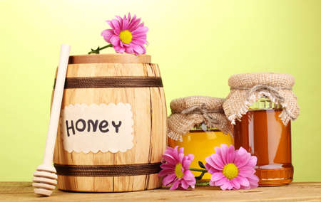 Sweet honey in barrel and jars with drizzler on wooden table on green background photo