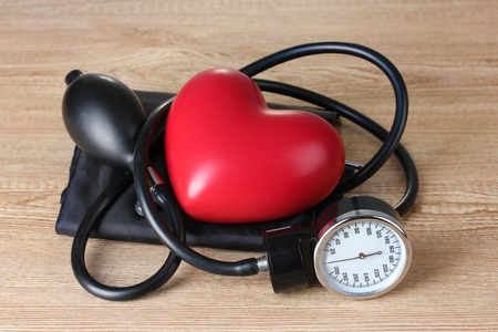 Black tonometer and heart on wooden background Stock Photo - 12665801