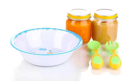 Jars of baby puree with plate, spoon and fork isolated on white photo