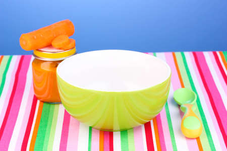 Jar of baby puree with plate and spoon on napkin on blue background photo