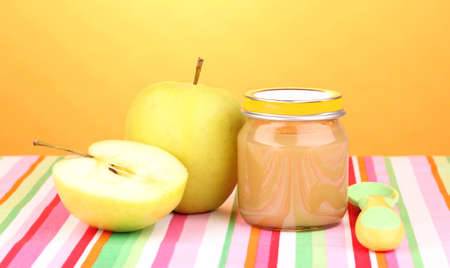 Jar of baby puree with spoon on napkin on yellow background photo