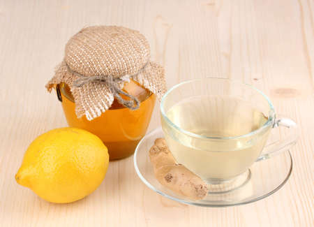 Healthy ginger tea with lemon and honey on wooden background photo