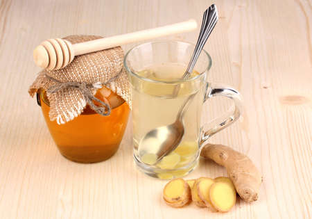 Healthy ginger tea with honey on wooden background photo