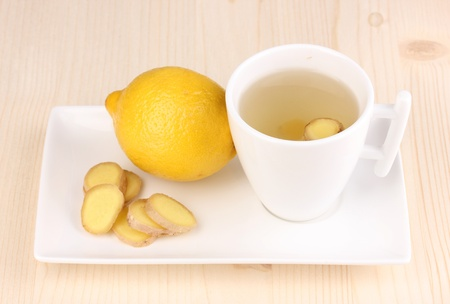 Healthy ginger tea with lemon on wooden background photo