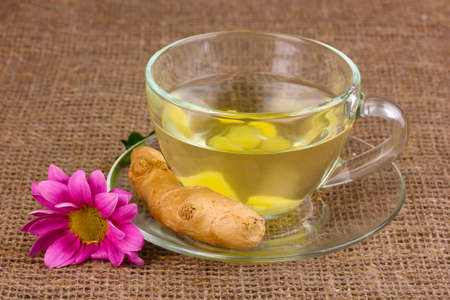 Healthy ginger tea and flower on sackcloth photo