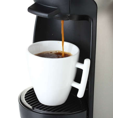 Espresso machine pouring coffee in cup isolated on white photo