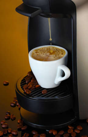 Espresso machine pouring coffee in cup on brown background photo