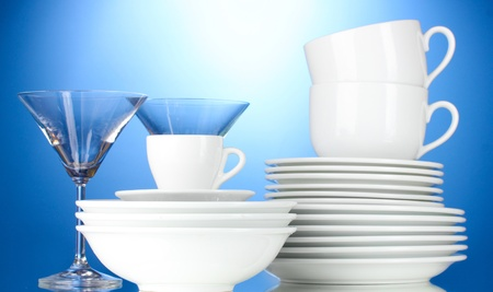 tableware: empty bowls, plates, cups and glasses on blue background