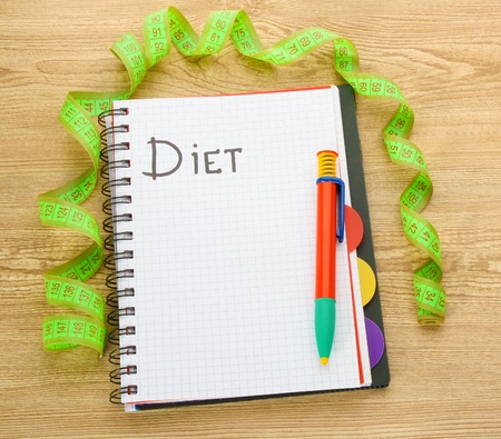 Planning of diet. Notebook measuring tape and pen on wooden table photo