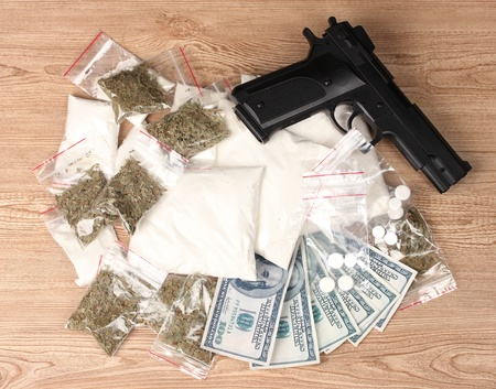 illegal drugs: Cocaine and marihuana in packages, dollars and handgun on wooden background Stock Photo