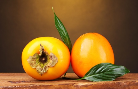 Two appetizing persimmons on wooden table on brown background photo