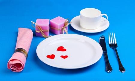 Table setting on blue background photo
