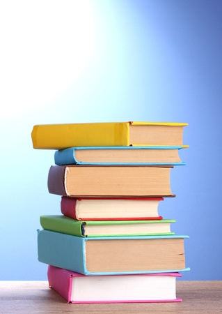 secretary tray: Stack of books on wooden table on blue background