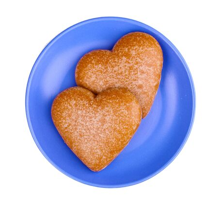 Heart-shaped cookies on saucer isolated on white photo