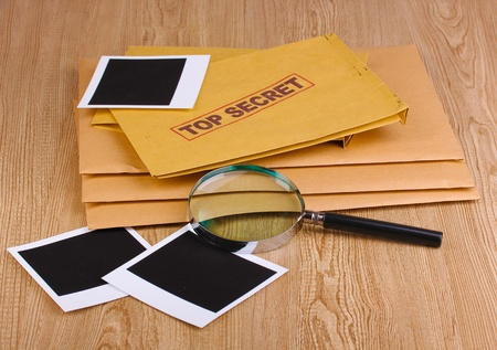 Envelopes with top secret stamp with photo papers and magnifying glass on wooden background Stock Photo - 12729256