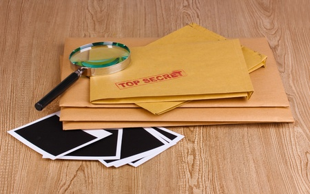 Envelopes with top secret stamp with photo papers and magnifying glass on wooden background Stock Photo - 12729238