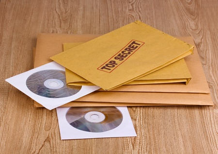 Envelopes with top secret stamp with CD disks on wooden background Stock Photo - 12729194
