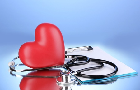 Medical stethoscope with clipboard and heart on blue background Stock Photo - 12731293