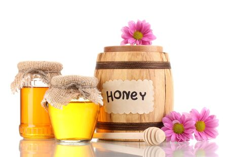 Sweet honey in barrel and jars with drizzler isolated on white photo