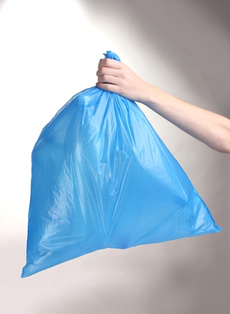 blue garbage bag with trash in hand isolated on white photo