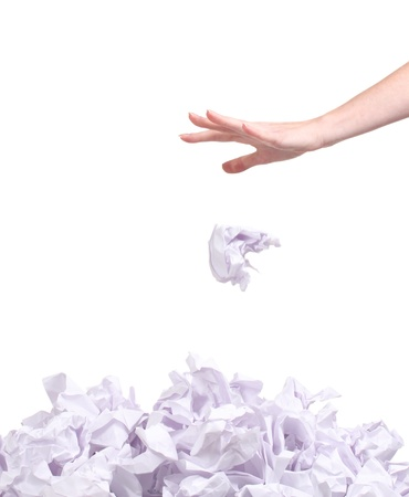 stack of crumpled paper balls and hand isolated on white photo