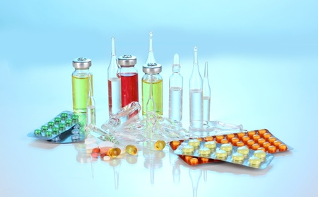 Tablets and ampoules on blue background photo