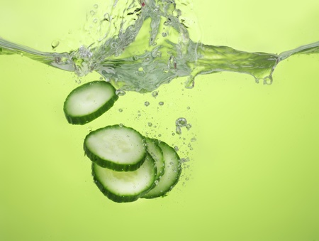 fresh sliced cucumber in water on green background photo