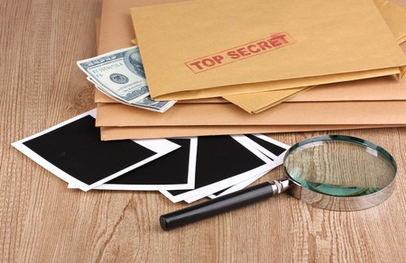 Envelopes with top secret stamp with photo papers and magnifying glass on wooden background Stock Photo - 12824782