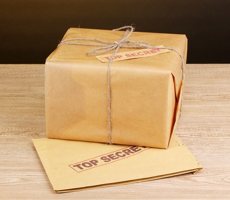 Parcel and envelope with top secret stamp on wooden table on brown background photo