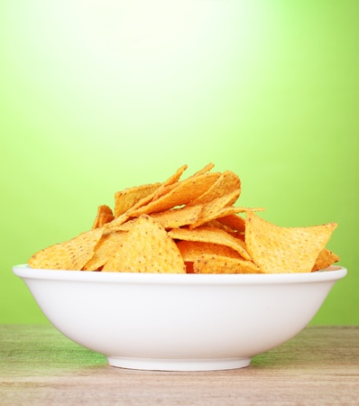 tasty potato chips in white  bowl on wooden table on green background photo