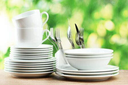 buffet table: Clean dishes on wooden table on green background