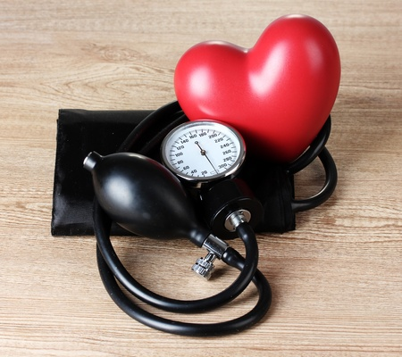 Black tonometer and heart on wooden background Stock Photo - 12824830