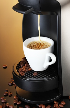 coffee machine: Espresso machine pouring coffee in cup on brown background