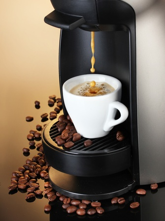 making coffee: Espresso machine pouring coffee in cup on brown background