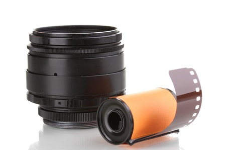 New photo film in cartridge and camera lens isolated on white photo
