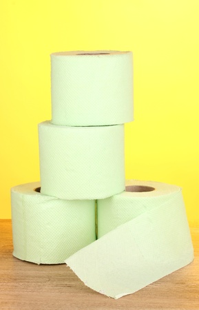 green rolls of toilet paper on wooden table on yellow background photo